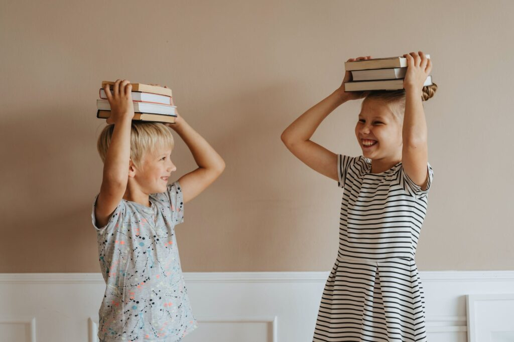 brother and sister with books on their heads